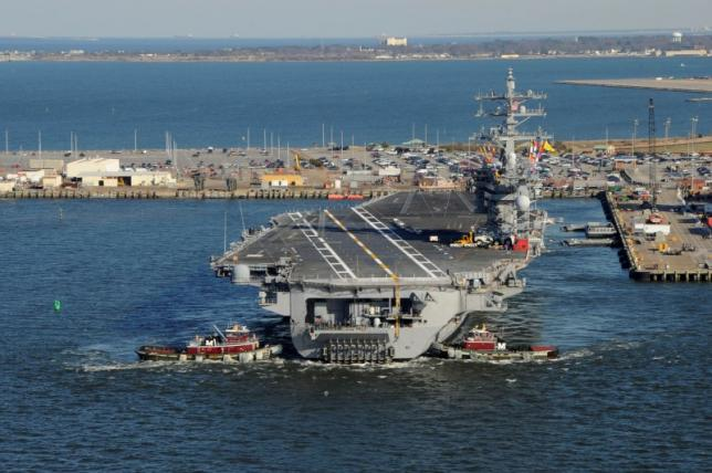 Tug boats assist the Nimitz-class aircraft carrier USS Dwight D Eisenhower (CVN 69) as it pulls away from the pier at Naval Station Norfolk, Virginia, in this handout photograph taken on February 21, 2013 and released on February 22. PHOTO: REUTERS