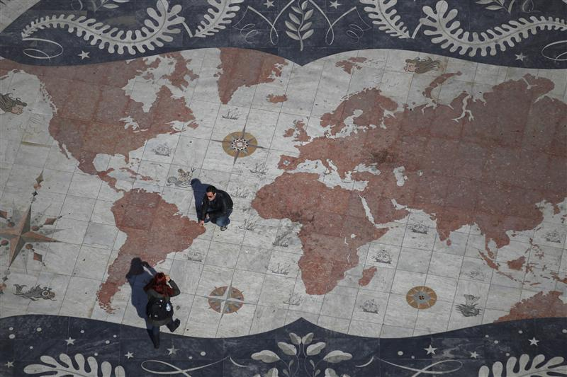 a man is photographed on a square decorated with a giant world map photo reuters