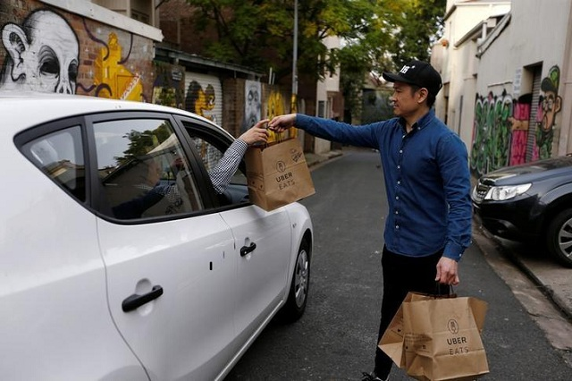 an uber driver takes delivery of bags of donuts destined for a customer via uber eats in sydney photo reuters