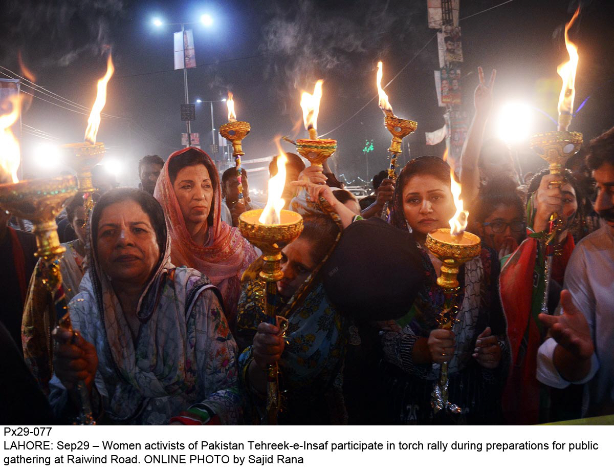 Women activists of PTI participate in torch rally during preperations for public gathering at Raiwind Road.  PHOTO: ONLINE