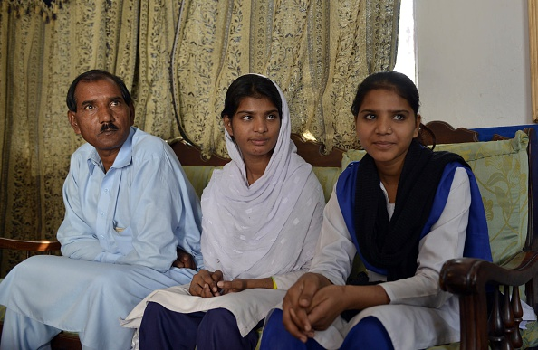 Ashiq Masih (L), the husband of Asia Bibi, a Pakistani Christian mother sentenced to death in under blasphemy laws, sits with daughters Esham (R) and Esha (C) at their residence in Lahore on October 31, 2014. PHOTO: AFP
