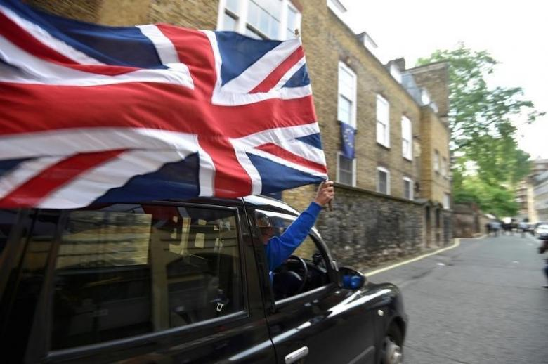 A taxi driver holds a Union flag, as he celebrates following the result of the EU referendum, in central London, Britain June 24, 2016. PHOTO: REUTERS