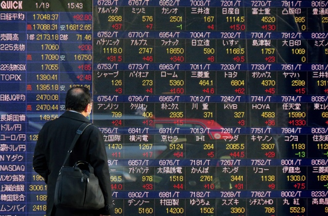 This file photo taken on January 19, 2016 shows a pedestrian looking at a screen showing movements for the Tokyo Stock Exchange in Tokyo. PHOTO: AFP