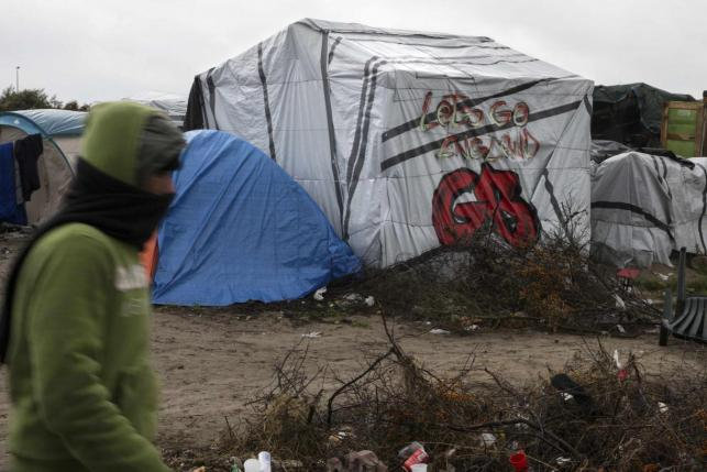 "A migrants walks past a tent with a graffiti reading ""Let's go England"" in the ""New Jungle"" makeshift camp as unseasonably cool temperatures arrive in Calais, northern France. PHOTO: REUTERS"