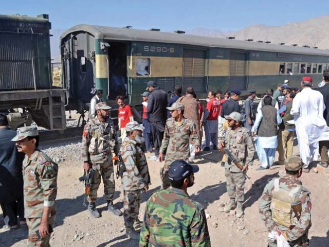 Security officials stand next to a compartment of the train hit by an IED blast in Mastung. PHOTO: AFP