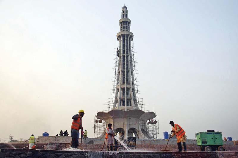 labourers clean the platform of minar e pakistan photo express