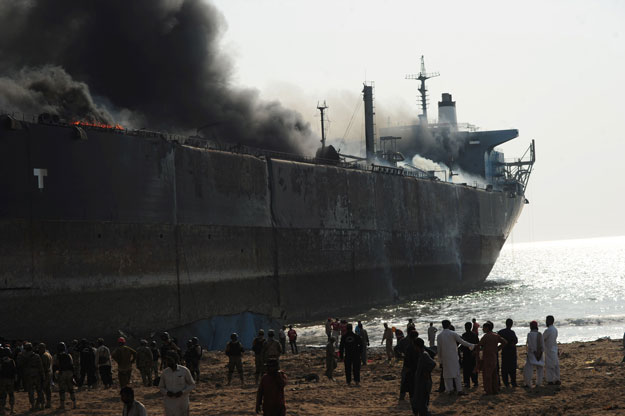 bystanders gather around the wreckage of a burning ship after a gas cylinder explosion at the Gadani shipbreaking yard, some 50 kilometres (30 miles) west of Karachi on November 1, 2016. PHOTO: AFP