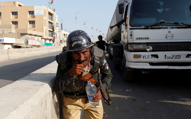 a policeman washes away the effects of tear gas fired by police after shias blocked the main national highway and railway tracks to protest the detention of their religious workers in karachi november 7 2016 photo reuters