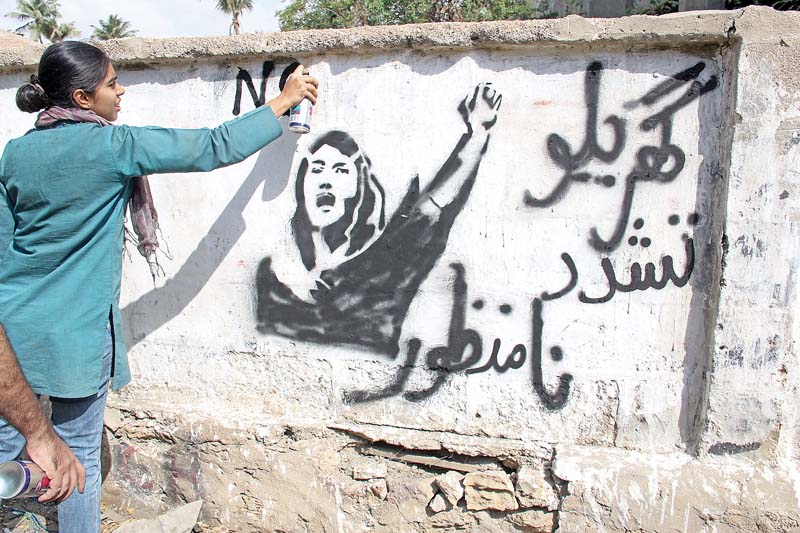 Young woman seen painting a slogan against domestic violence in Karachi. PHOTO: AYESHA MIR/EXPRESS