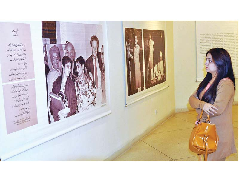 a woman admires artworks on display at alhamra for faiz international festival photo app