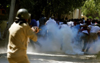 Protesters run away as a policeman fires tear gas towards them during a protest against the recent killings in Kashmir, on the outskirts of Srinagar, August 5, 2016. PHOTO: REUTERS