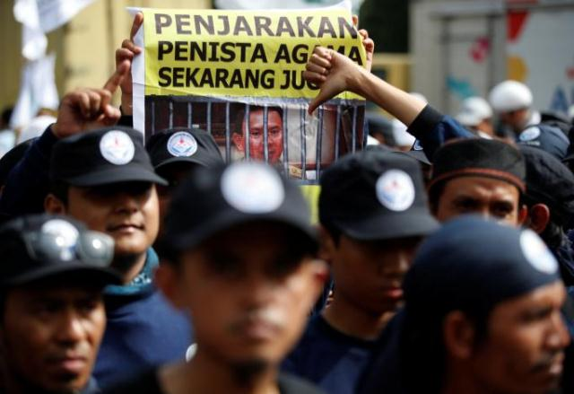 a protester holds a banner outside a court during the first day of the blasphemy trial of jakarta 039 s governor basuki tjahaja purnama also known as ahok in jakarta indonesia december 13 2016 photo reuters