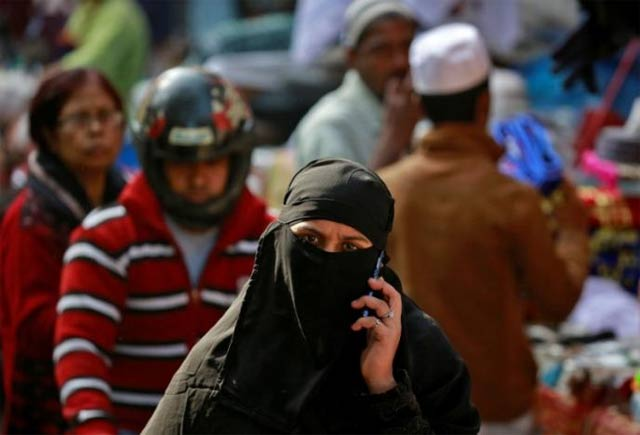a muslim woman speaks on her mobile phone as she walks through a market in delhi photo reuters