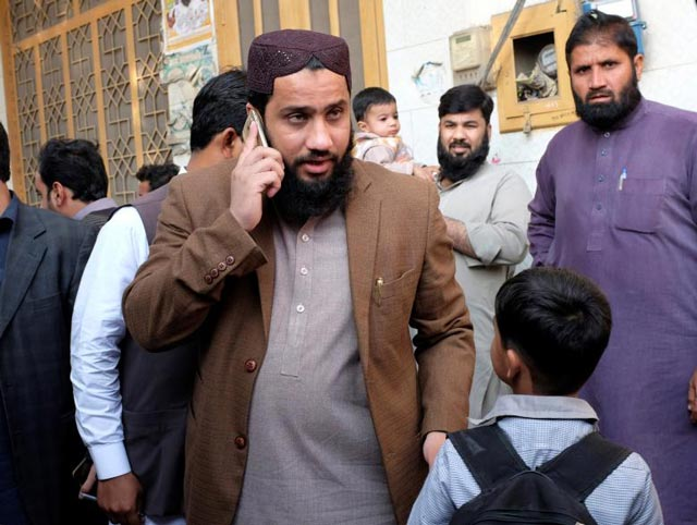 masroor nawaz jhangvi a muslim cleric whose father was one of pakistan 039 s most infamous sectarian figures uses his mobile phone while meeting residents in jhang december 16 2016 photo reuters