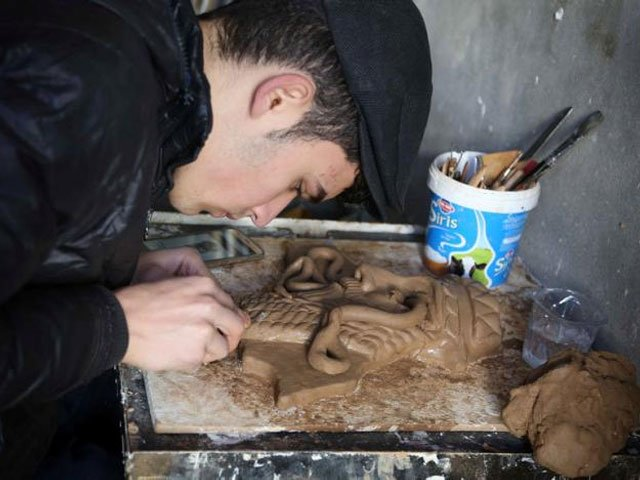 Ninos Thabet, an 18-year-old Christian who studied art at Mosul University, creates miniature replicas of statues destroyed by militants when they overran the 3,000-year-old Assyrian city of Nimrud 2-1/2 years ago, in Erbil, Iraq, January 13, 2017. Picture taken January 13, 2017. REUTERS/Girish Gupta