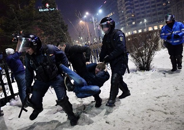 romanian riot police evacuate a protester during a demonstration against controversial decrees to pardon corrupt politicians and decriminalize other offenses in front of the government headquarters in bucharest on february 1 2017 photo afp