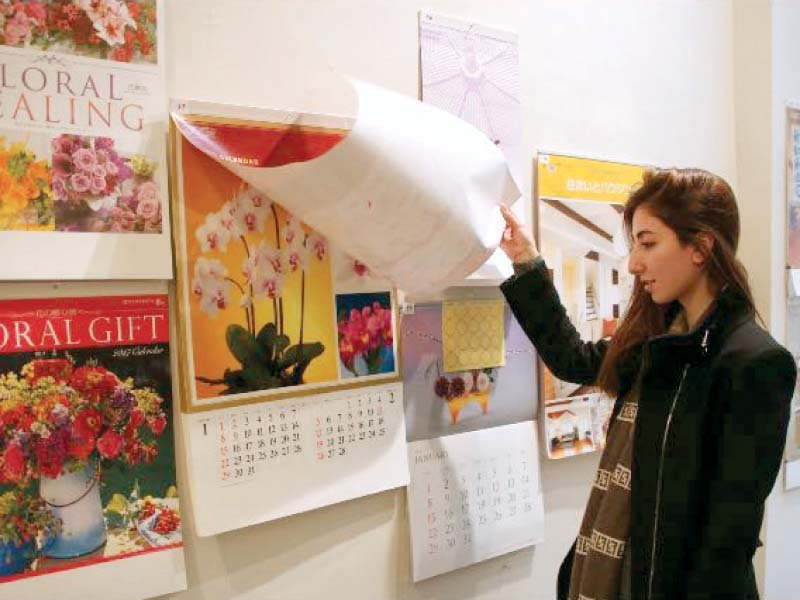 a woman looks at japanese calendars on display at national art gallery photo express