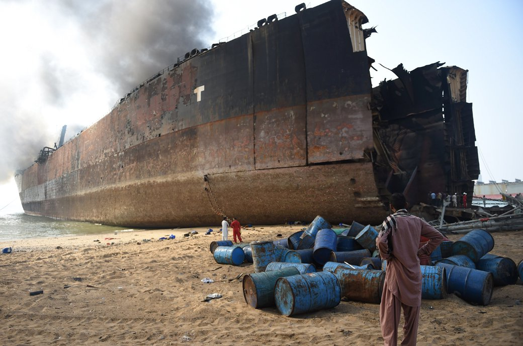 a man looks at the wreckage of a burning ship a day after a gas cylinder explosion at the gadani shipbreaking yard on november 2 2016 photo afp