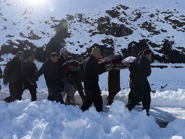 afghan men carry the body of a victim of avalanches after funeral prayers in khench district of panjshir province north of kabul on february 26 2015 photo afp