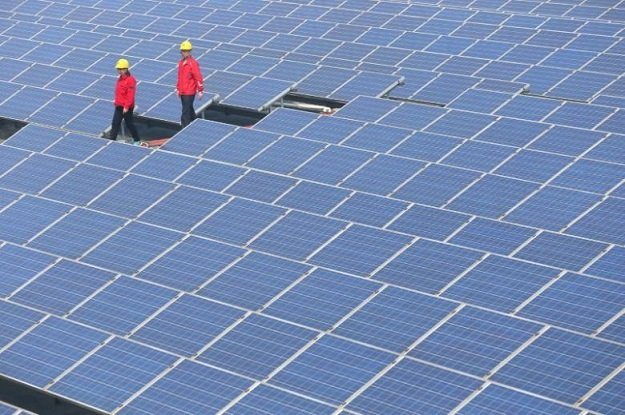 workers walk past solar panels in jimo shandong province china april 21 2016 photo reuters