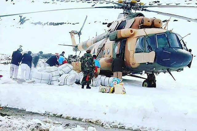 afghan survivors of an avalanche look on as an afghan army helicopter delivers relief goods in the village of hafsa in nuristan province photo afp
