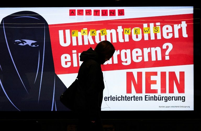 people walk by an electoral poster at zurich station which reads quot uncontrolled citizenship no quot ahead of a vote on citizenship photo afp