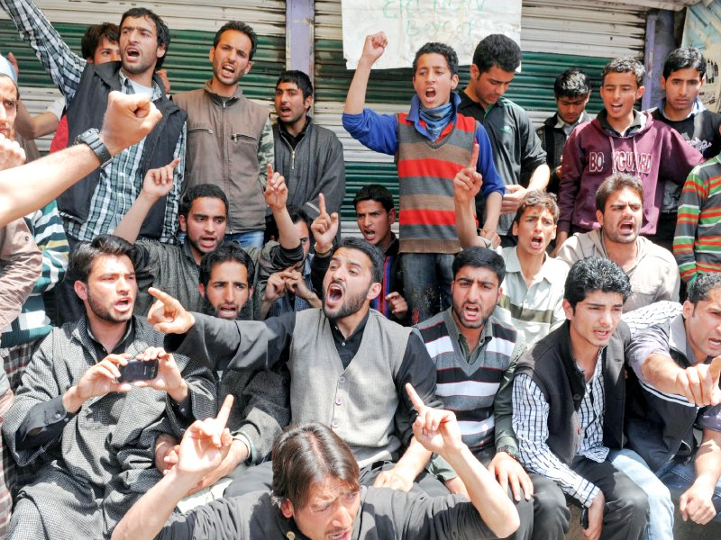 kashmiri muslim youth shout pro freedom and anti election slogans during a protest outside a polling station at kangan in srinagar photo afp