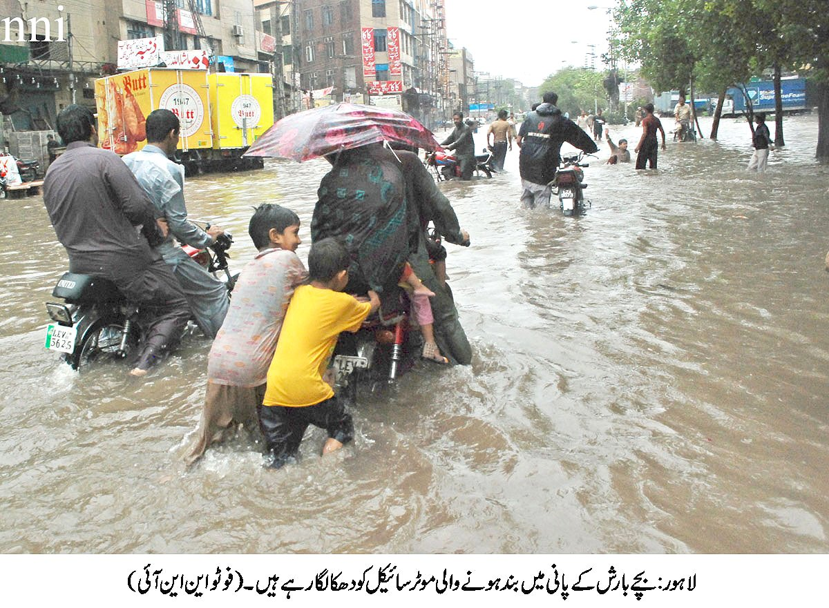 children pushing a motorbike as it struggles to make way in floodwaters in lahore photo nni
