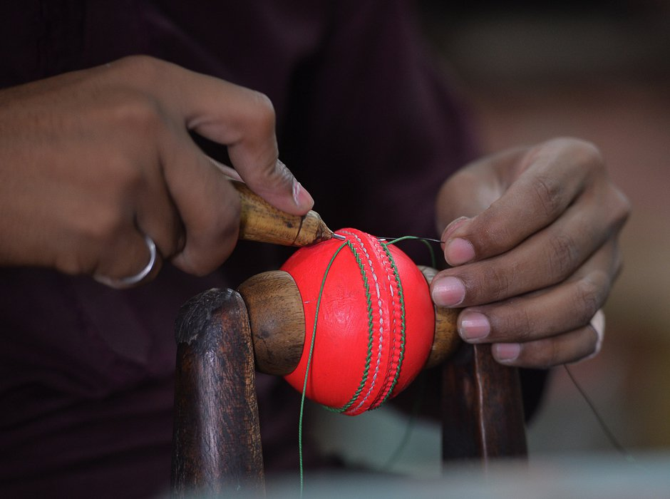 a pakistani worker stitches a pink cricket ball at the grays of cambridge factory in sialkot pakistan 039 s sports goods industry is positioning itself to be the prime manufacturer of pink cricket balls    a high visibility alternative for use in day night test matches aimed at dragging the game into the 21st century photo afp
