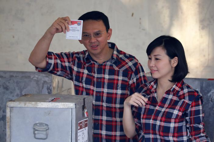 governor of indonesia 039 s capital basuki tjahaja purnama l shows his ballot as he stands beside his wife veronica tan during an election for jakarta 039 s governor in jakarta indonesia february 15 2017 photo reuters
