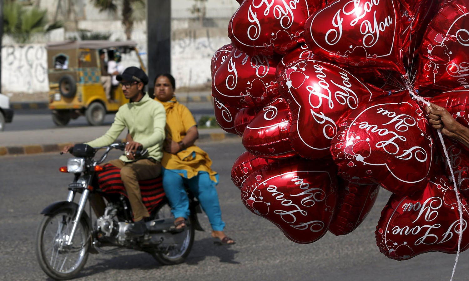 a couple on a motorcycle ride past a vendor selling heart shaped balloons on valentine 039 s day photo reuters