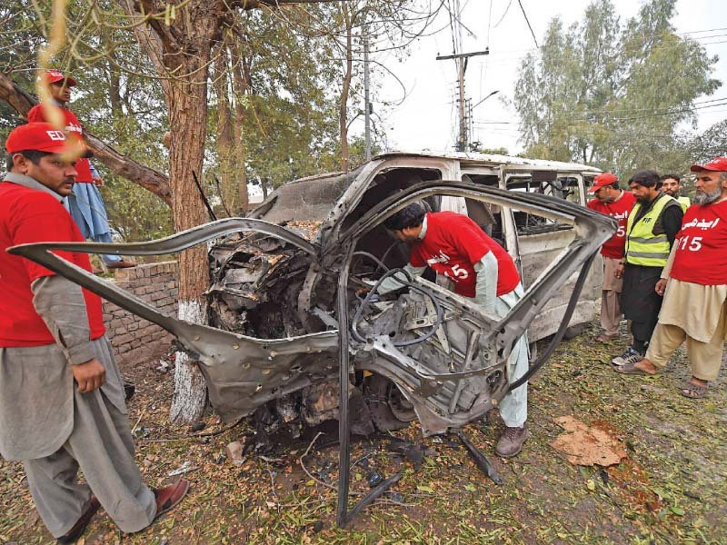 volunteers inspect the mangled heap of a van targeted in the peshawar suicide attack a photo of the three levies men killed in the mohmand bombings photo afp express