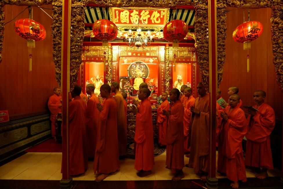 buddhist monks pray inside a temple during the lunar new year 039 s eve celebrations in chinatown in bangkok thailand reuters jorge silva