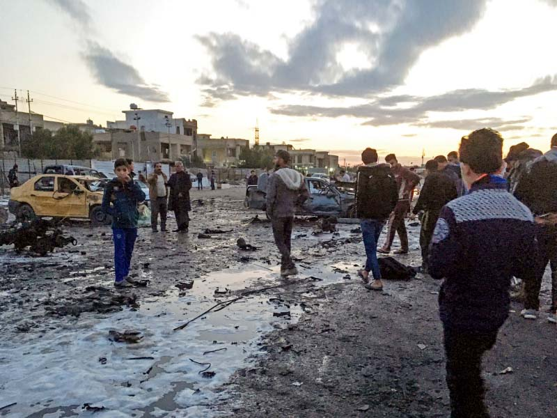 iraqis sift through debris at the scene of the massive car bombing in baghdad photo afp