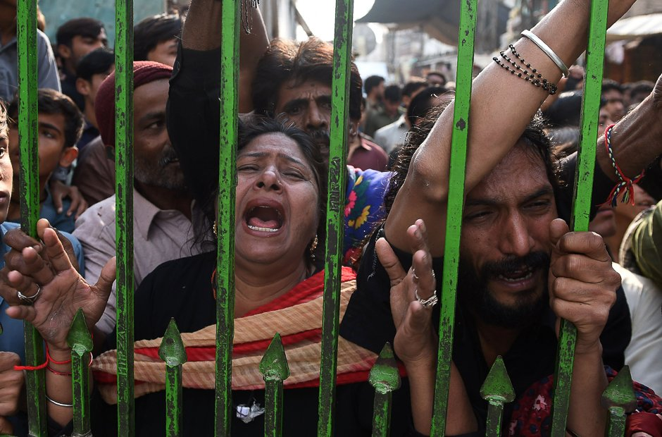 mourners gather outside closed gate of the lal shahbaz shrine photo afp