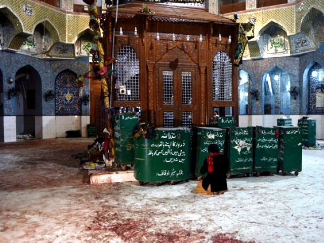 a devotee sits on the blood stained floor a day after a bomb attack hit the 13th century sufi shrine of lal shahbaz qalandar in the town of sehwan in sindh on february 17 2017 photo afp
