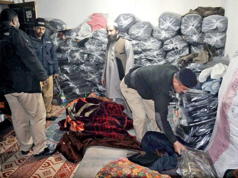 policemen search a warehouse in the remits of city police station in rawalpindi photo ppi