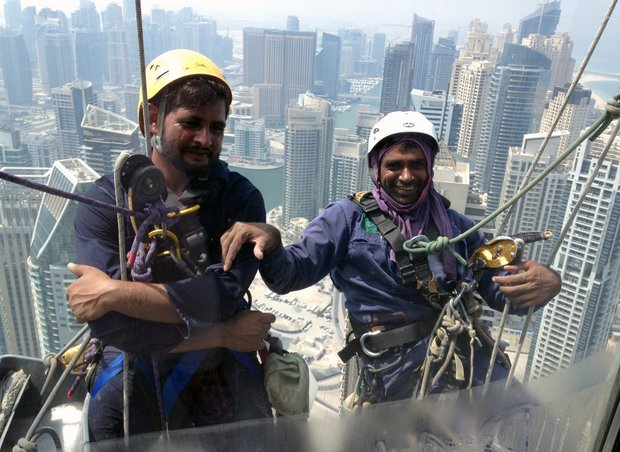 pakistani window cleaners work on a building in the gulf emirate of dubai on 6 september 2014 photo afp