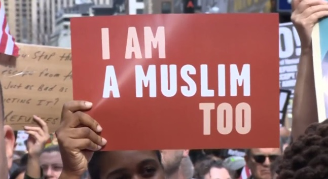 holding placards featuring a hijabi woman in an american flag captioned we the people are greater than fear and signs reading i am a muslim too the demonstrators paraded around new york s most famous spot screengrab