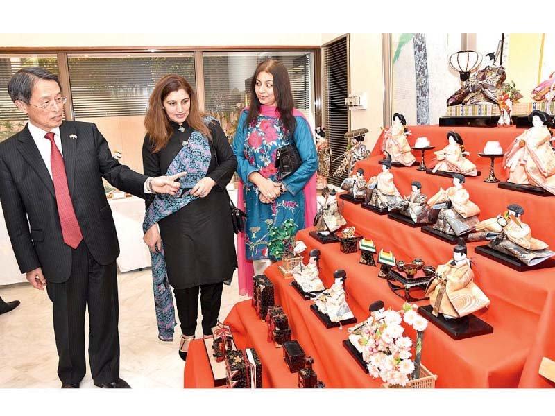 japanese ambassador takashi kurai explains the characters of various dolls on display at his home photo app