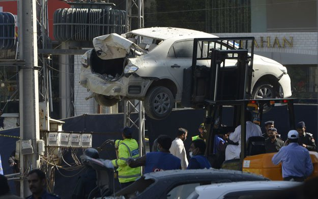 officials move a damaged car from the site after a bomb attack in lahore on february 23 2017 photo afp
