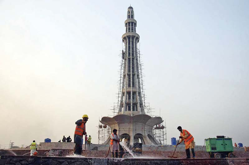 labourers clean the platform of minar e pakistan photo express