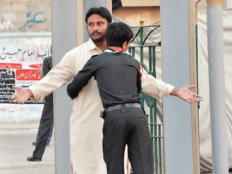 a volunteer frisks a man outside the shah e khurasan imambargah on monday security outside imambargahs has been increased with walkthrough gates installed at a considerable distance from the mosques photo express