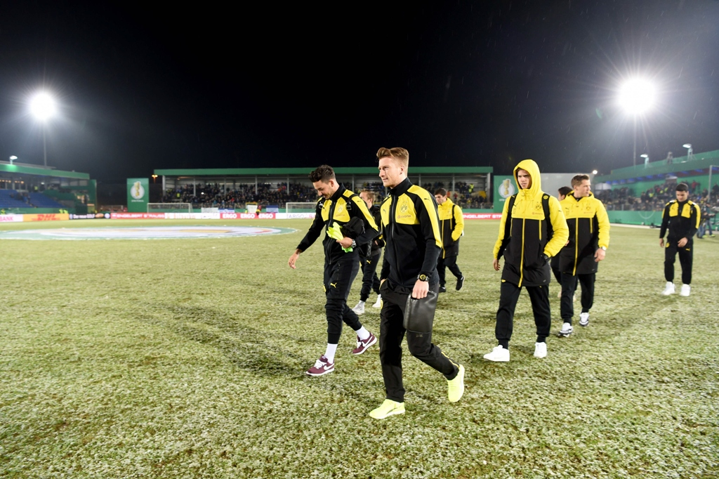dortmund players walk over the pitch after the match was cancelled on february 28 2017 photo afp