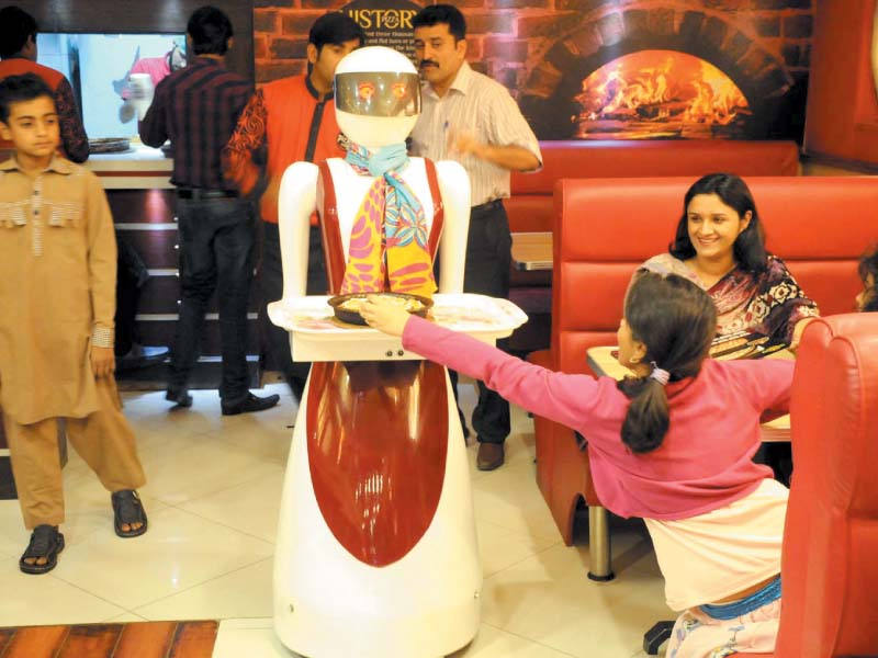 customers wait anxiously to be served by the robot waiter at pizza com photo inp