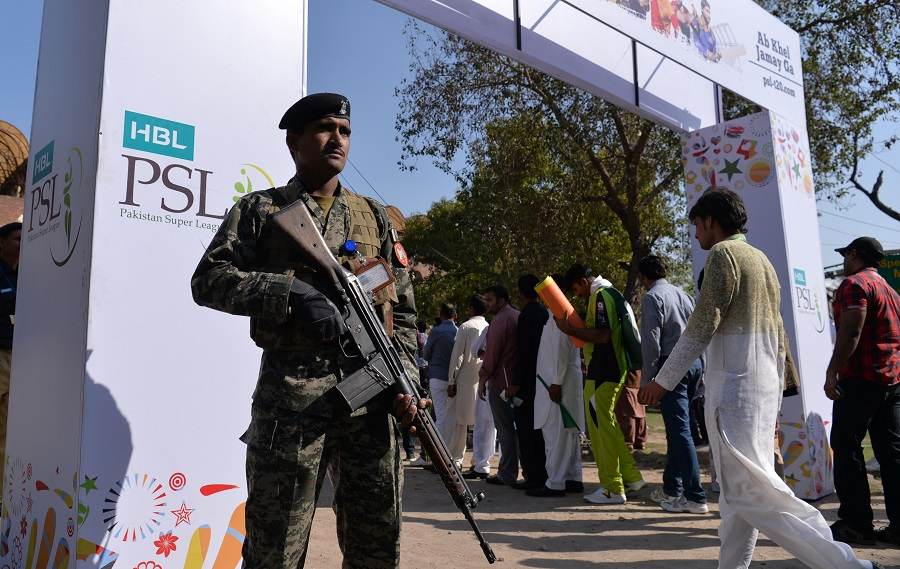 Pakistani soldier patrol as spectators queue at an entry gate of The Gaddafi Cricket Stadium in Lahore on March 5, 2017. PHOTO: AFP