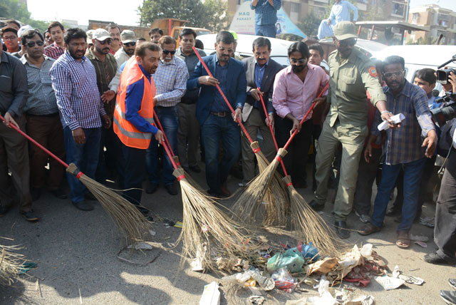 MQM Pakistan leaders cleaning the city's roads as part of their campaign. PHOTO: FILE