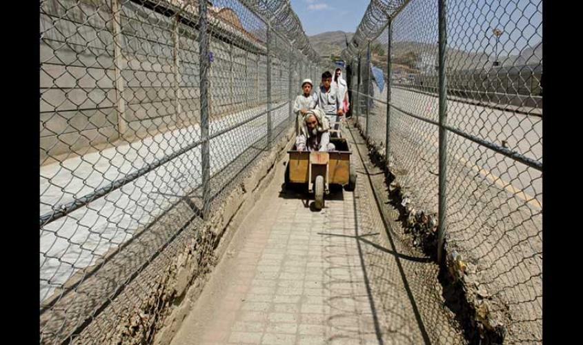 Men coming from Afghanistan move down a corridor between security fences at the border post in Torkham, Pakistan on the Durand Line on 18 June 2016. PHOTO: REUTERS