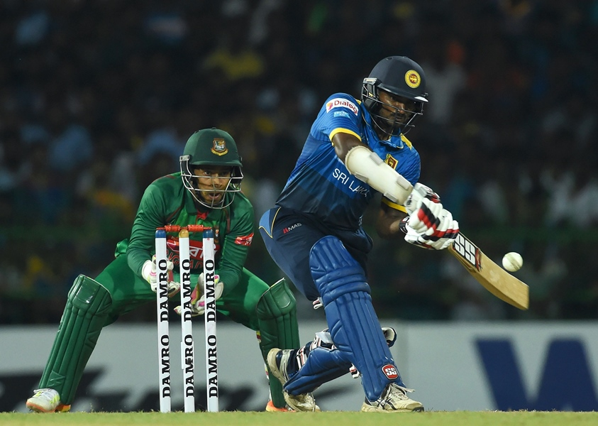 sri lankan cricketer kusal perera plays a shot as bangladesh wicketkeeper mushfiqur rahim l looks on during the first t20 international cricket match between sri lanka and bangladesh at the r premadasa stadium in colombo on april 4 2017 photo afp