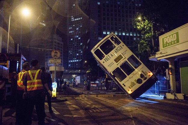 driver arrested after hong kong tram flips over injuring 14